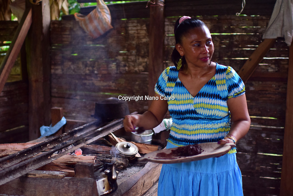 Virgilia, mother of a Bribri family, preparing natural cacao drink at tribe house. <br />