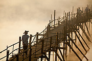 Man with traditional hat crossing Thandwe river on U Wa wooden bridge, morning mist and fog