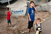 Greece, Lagkadikia, Refugee Camp, Mohamad, age 12 and his brothers Abdul Rahman age 6, and Abdulla age 1,5. Staying at the back of their tent. Hayfa Sadiq, age 34, stays with her five boys age between 1,5 and 15 at the camp in this camps since April 2016. Judi, age 15, Mohamad, age 12,  Shahin, age 9, Abdul Rahman, age 6, Abdulla, age 1,5.Her husband and the father of all five kids, Mazkin, age 42, is living in Berlin, Germany. He is accepted as refugee seeking asylum. They family is form Haseki, North Syria.