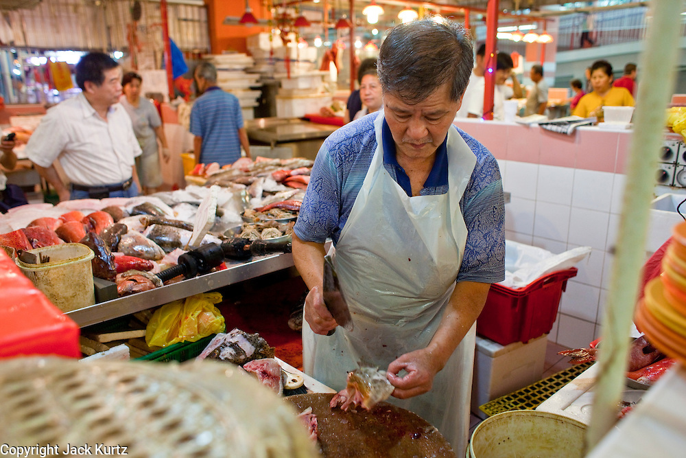 "Apr. 28 -- SINGAPORE:   A butcher chops chicken in a ""wet"" market in Chinatown in Singapore.    PHOTO BY JACK KURTZ"