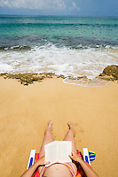 Woman sitting in a beach chair on a sandy beach, North Shore of Kauai, Hawaii, USA.