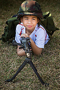 "11 JANUARY 2014 - BANGKOK, THAILAND:  A Thai boy plays with a machine gun during Children's Day in Bangkok. The Royal Thai Army hosted a ""Children's Day"" event at the 2nd Cavalry King's Guard Division base in Bangkok. Children had an opportunity to look at military weapons, climb around on tanks, artillery pieces and helicopters and look at battlefield medical facilities. The Children's Day fair comes amidst political strife and concerns of a possible coup in Thailand. Earlier in the week, the Thai army announced that movements of armored vehicles through Bangkok were not in preparation of a coup, but were moving equipment into position for Children's Day.     PHOTO BY JACK KURTZ"