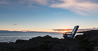 Two wood chairs sit on the rocks at McMicking Point in Victoria, BC and are the perfect place for a couple to watch the sunset.
