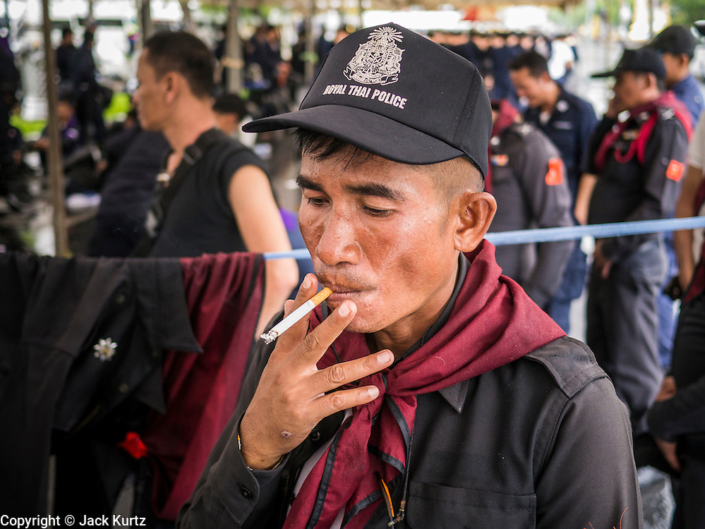 23 NOVEMBER 2012 - BANGKOK, THAILAND:   A Thai riot policeman smokes a cigarette during a break from duty guarding Government House in Bangkok against anti-government protesters. Thai authorities have imposed the Internal Security Act (ISA), that enables police to call on the army if needed to keep order, and placed thousands of riot police in the streets around Government House in anticipation of a large anti-government protest Saturday. The group sponsoring the protest, Pitak Siam, said up to 500,000 people could turn out to protest against the government. They are protesting against corruption in the current government and the government's unwillingness to arrest or pursue fugitive former Prime Minister Thaksin Shinawatra, deposed in 2006 coup and later convicted on corruption charges. The current Thai Prime Minister is Yingluck Shinawatra, Thaksin's sister.     PHOTO BY JACK KURTZ