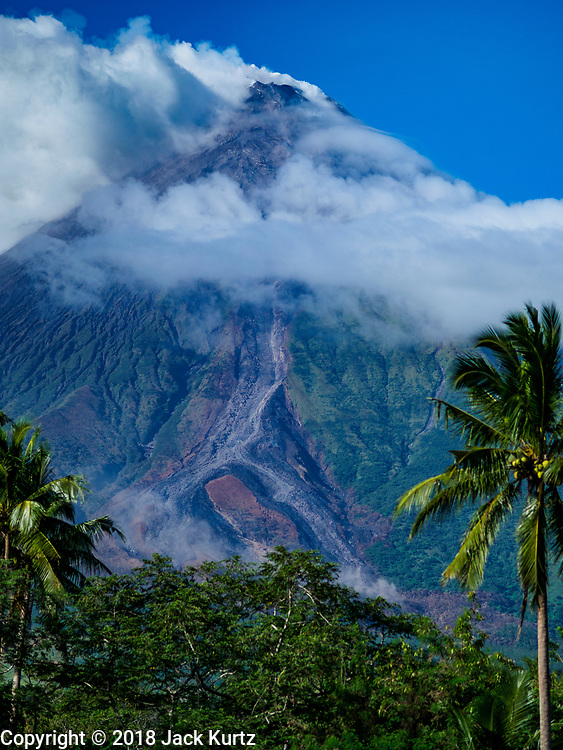 21 JANUARY 2018 - CAMALIG, ALBAY, PHILIPPINES: As seen from a small clearing near the evacuation zone, the Mayon volcano, releases smokes and ash Sunday afternoon. Mayon is the most active volcano in the Philippines. More than 30,000 people have been evacuated from communities on the near the Mayon volcano in Albay province in the Philippines. Most of the evacuees are staying at schools in communities outside of the evacuation zone.   PHOTO BY JACK KURTZ