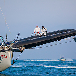After the finish:<br /> Larry Ellison on the helm with James Spithill, <br /> Race1<br /> 2010 America's Cup, Valencia<br /> ©2010 Kaufmann/Forster go4image.com