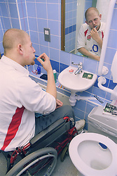 Young man; who is a wheelchair user; brushing his teeth in purposebuilt bathroom in bedsit at direct access hostel for homeless and vulnerably housed young people,