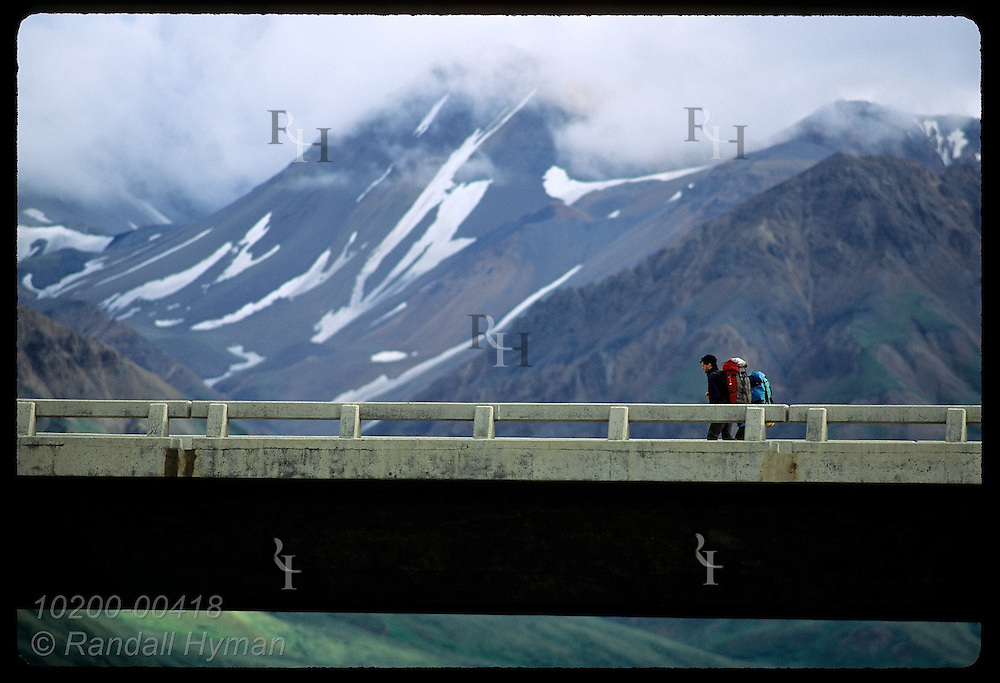 Backpackers cross Savage River bridge against backdrop of cloudy Alaska Range; Denali National Park. Alaska