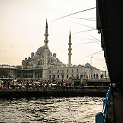 Hidayet Cami in Eminonu as seen from Galata Bridge in the late afternoon. Rows of fishermen line the Galata Bridge--the silhouettes of their fishing rods can be seen at top