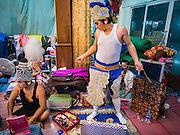 "30 JANUARY 2016 - NONTHABURI, NONTHABURI, THAILAND: A performer puts on his costume before a ""likay"" show at Wat Bua Khwan in Nonthaburi, north of Bangkok. Likay is a form of popular folk theatre that includes exposition, singing and dancing in Thailand. It uses a combination of extravagant costumes and minimally equipped stages. Intentionally vague storylines means performances rely on actors' skills of improvisation. Like better the known Chinese Opera, which it resembles, Likay is performed mostly at temple fairs and privately sponsored events, especially in rural areas. Likay operas are televised and there is a market for bootleg likay videos and live performance of likay is becoming more rare.     PHOTO BY JACK KURTZ"