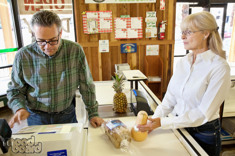 Mature owner with senior female customer at checkout counter in grocery market