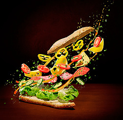Exploding pepperoni sandwich baguette with lettuce, tomatos, cheese and spring onions.<br /> <br /> Available for Sale in Archive Image Library.