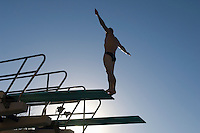 Swimmer standing on diving board at sunset