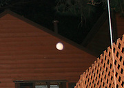 A peach colored orb floating over a pool fence at dark.