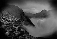 Sulphurous gas rises from vents beside Ijen crater's acidic lake.  Java, Indonesia.