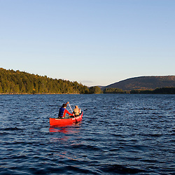 A woman and her son paddle a canoe on Prong Pond in Maine USA (MR)