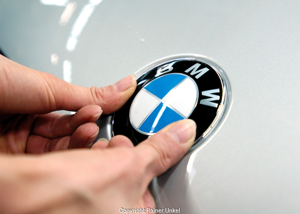 DEUTSCHLAND : Autoproduktion bei BMW in Regensburg : ein BMW-Emblem wird angebracht.   GERMANY : Car production at BMW in Regensburg : an emblem is installed.   17.04.2007.   Foto: Copyright by Rainer UNKEL, Tel.: (0)228/477211, Fax: (0)228/477212.