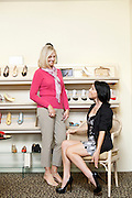 Happy mid adult woman trying on heels while mature female looking in shoe store