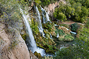 Rifle Falls State Park, Garfield County, Rifle, Colorado, USA. East Rifle Creek plunges over a travertine dam into a triple 70-foot waterfall. Nearby limestone cliffs feature some small caves and three species of bats.