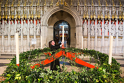 © Licensed to London News Pictures. 27/11/2015. York UK. Head Verger Alex Carberry places the last candle in One of the largest Advent wreaths in the country that has been put in place at York Minster marking the start of the cathedral's Advent & Christmas festivities. The wreath measures 3 metres wide & holds five candles each 1 metre tall capable of burning constantly for three weeks. The candles represent the people who waited for the coming of Christ, with the fifth candle representing the birth of Christ. Photo credit: Andrew McCaren/LNP