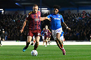 Luke Woolfenden (28) of Ipswich Town battles for possession with Ellis Harrison (22) of Portsmouth during the EFL Sky Bet League 1 match between Portsmouth and Ipswich Town at Fratton Park, Portsmouth, England on 21 December 2019.
