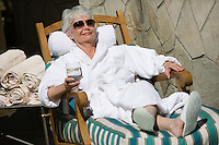 Senior woman wearing bathrobe, relaxing outdoors
