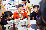 An instructor at the Development Center for Human Resources and Product Industry Enterprises or (Balai Pengembangan SDM & Produk IKM), demonstrate how to operate a sewing machine to a group of students.  Semarang, Indonesia.  May 14, 2013.