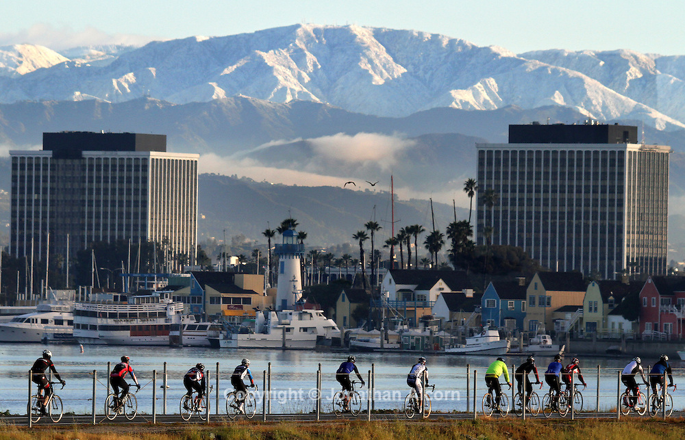 Bicyclists ride on the bike path in Marina Del Rey with snowcapped mountains as a backdrop as a cold winter storm moves out of the Southern California area on Sunday, February 20, 2011.