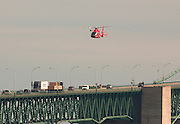 A Coast Guard helicopter searches the water along the west side of the Mackinac Bidge for a woman who reportedly either fell or jumped from the bridge.