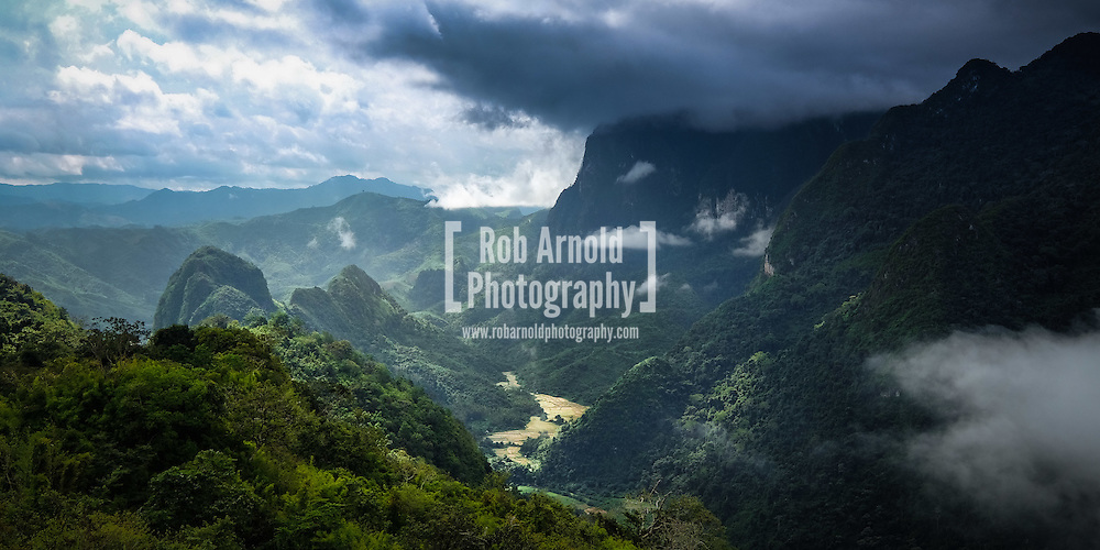Rice paddy fields nestled in a valley surrounded by forested mountains and forming clouds in Northern Laos