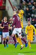 Marvin Bartley (#6) of Livingston FC jumps into Steven Naismith (#14) of Heart of Midlothian FC and they clash heads during the Ladbrokes Scottish Premiership match between Heart of Midlothian FC and Livingston FC at Tynecastle Park, Edinburgh, Scotland on 4 December 2019.