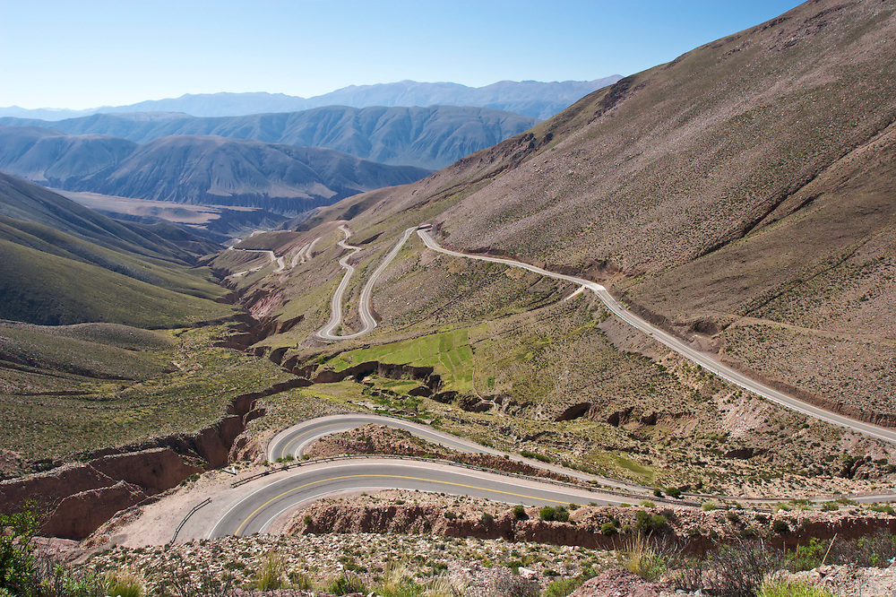 A mountain road winds around a giant fissure in the landscape, in the high desert of northern Argentina.