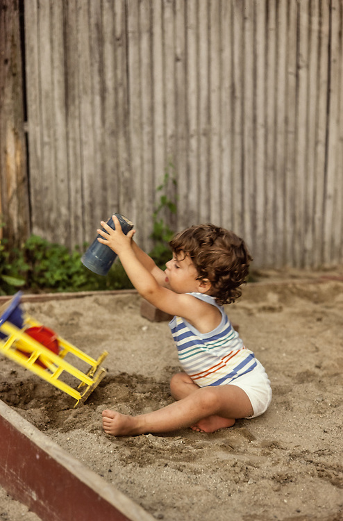 toddler playing in sand box