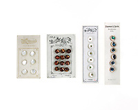 Antique button cards with mother-of-pearl and glass buttons on a white background.