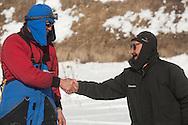 Iditarod leader John Baker of Kotzebue shakes hands with former checkpoint checker Howard Lincoln in White Mountain.