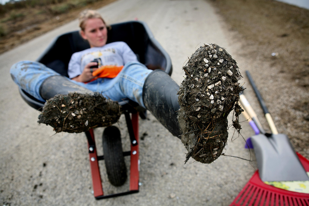 Marissa Berg, 12, relaxes in a wheelbarrow while her family tries to salvage items from their home in Sabine Pass that was destroyed by Hurricane Ike Friday September 19, 2008.