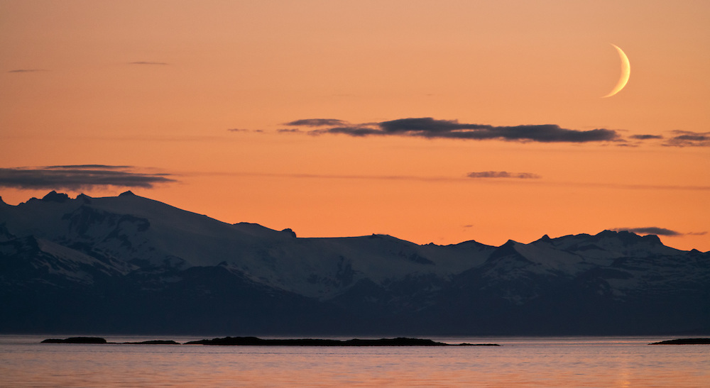 Moonrise at sunset over silhouetted mountains looking out from Kake on Kupreanof Island in the Inside Passage of Southeast Alaska. Evening. Summer.