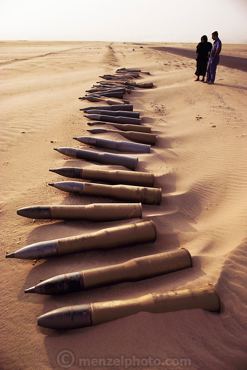 Artillery shells on road to Umm-Qadeer, Kuwait. Huge amounts of munitions were abandoned in Kuwait by retreating Iraqi troops in February, 1991. Also, nearly a million land mines were deployed on the beaches and along the Saudi and Iraqi border. In addition, tens of thousands of unexploded bomblets (from cluster bombs dropped by Allied aircraft) littered the desert. July 1991.