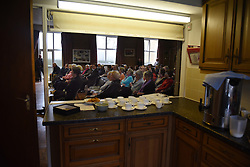 "© London News Pictures. ""Looking for Nigel"". A body of work by photographer Mary Turner, studying UKIP leader Nigel Farage and his followers throughout the 2015 election campaign. PICTURE SHOWS - The audience listen to Nigel Farage speaking, as seen through the kitchen hatch, with tea and digestive biscuits laid out, during a public meeting in Cliffsend Village Hall, near Ramsgate, Kent on March 28th 2015. . Photo credit: Mary Turner/LNP **PLEASE CALL TO ARRANGE FEE** **More images available on request**"