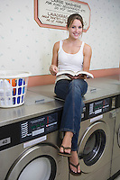 Portrait of young woman sitting on washing machine
