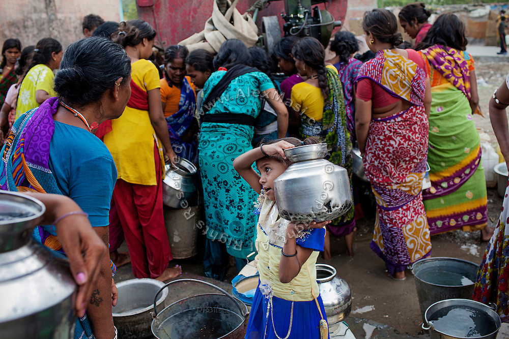 A girl is busy collecting potable drinking water delivered by a government truck in Oriya Basti, one of the water-affected colonies near the abandoned Union Carbide (now DOW Chemical) industrial complex in Bhopal, Madhya Pradesh, central India.