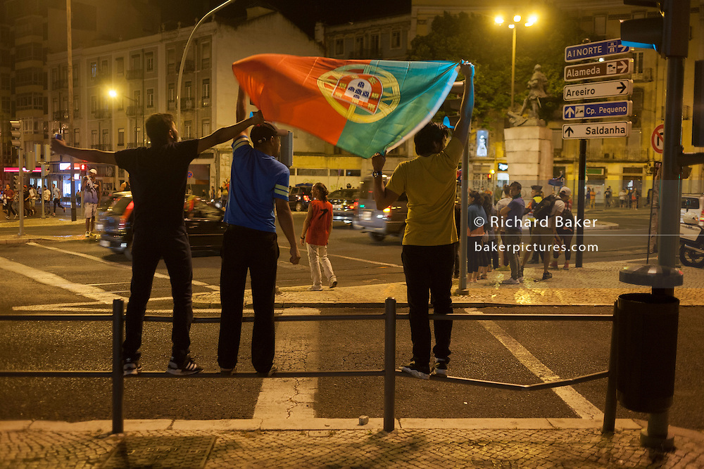 Portuguese football fans celebrate their country's victory over France in the Euro 2016 tournament final on 10th July 2016, in Lisbon, Portugal. Waving their national flag above their heads, they wave to passers-by after the final whistle in the game that captivated Portugal with their hero, Christiano Ronaldo the symbol of their well-being and patriotism. (Photo by Richard Baker / In Pictures via Getty Images)