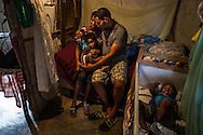 "SABANETA DE YÁSICA - JUNE 28, 2015: Robert Rosario Almonte, 24, a Dominican, and his wife Yoselin Bernard, 24, who was born in the Domincan Republic to Haitian parents with a midwife at their home, pose for a portrait with their two children, Daniel Angel Rosario Bernard, 3, and Dariel Rosario Bernard, 1, at their humble home, built of tree branches, sheetmetal and cardboard, in the La Catalina neigborhood. Yoselin and their children are unable to get identification papers because she never got a birth certificate since she was not born in a hospital.  If the police find her, they will legally be able to deport her and their children to Haiti under law 169-14. She is very frightened and rarely leaves their home. She said she does not know which country she belongs to, because neither Haiti nor The Dominican Republic will give her documents. She said she feels like she doesn't have a country, that she is just up in the air"". PHOTO: Meridith Kohut for The New York Times"