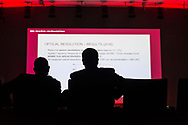 Two men are silhouetted against a screen full of text during a presentation at an event held at the Bella Center in Copenhagen