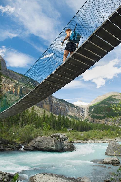 Hiker crossing suspension bridge on the Berg Lake Trail, Mount Robson Provincial Park British Columbia Canada