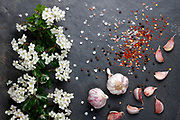 Early summer white  flower blossoms with pink garlic and Himalayan rock salt with pepper and chilli on slate