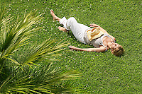 Middle-aged woman sleeping on grass high angle view