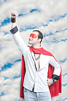 Young man in superhero costume with hand raised against cloudy sky