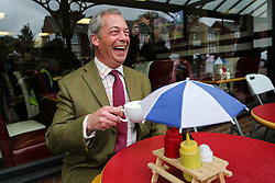 © Licensed to London News Pictures. 25/05/2016. Chapeltown, UK. Nigel Farage enjoys a cup of tea in Chapeltown, South Yorkshire, during the UKIP Referendum open top bus in tour. The party's purple open top battle bus is touring the country in the run up to the EU referendum. There is just a month to go until the UK's referendum on it's membership of the European Union. Poll stations will open their doors on Thursday 23 June. Photo credit : Ian Hinchliffe/LNP