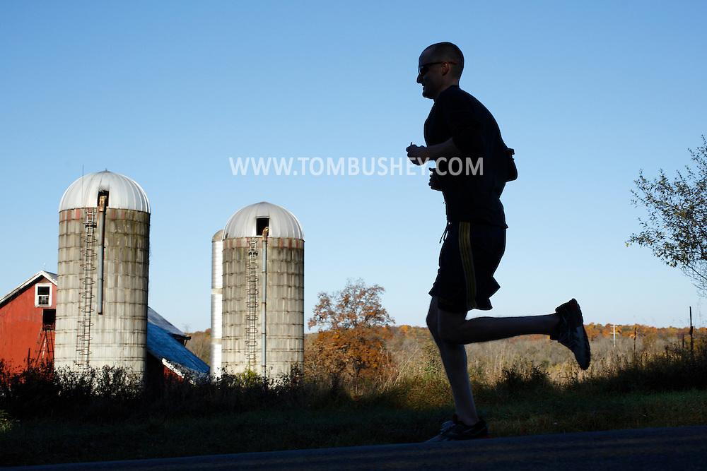 Goshen, New York  - A runner races past a barn and silos in the Hambletonian Marathon on Sunday, Oct. 20, 2013.